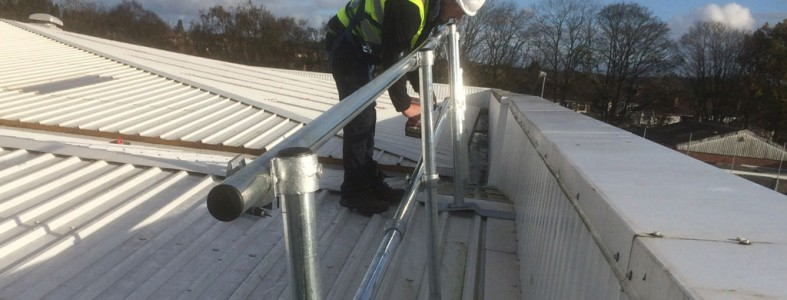 Installing steel tube roof edge protection using key clamps on a factory roof